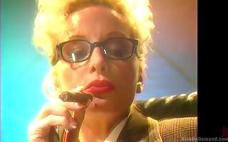 Blonde mature lady with glasses smokes a cigar and plays with her tits