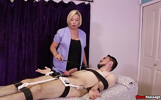Strict blonde masseuse gives a Femdom handjob to a borders consumer